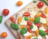 Pinsa crudaiola con pomodorini colorati, mozzarella di bufala e colatura di alici